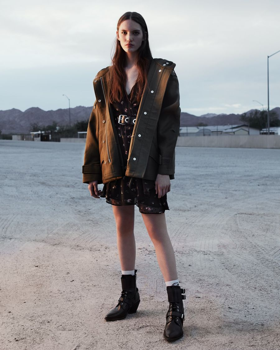 Image of a woman standing outside wearing a khaki jacket opened over a short printed dress and leather boots.