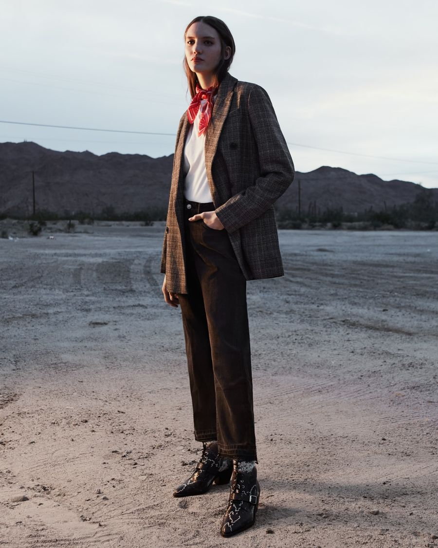 Woman standing in the desert at sunset wearing a white t-shirt with a grey checked blazer, black jeans, snake printed boots and a red scarf around her neck.