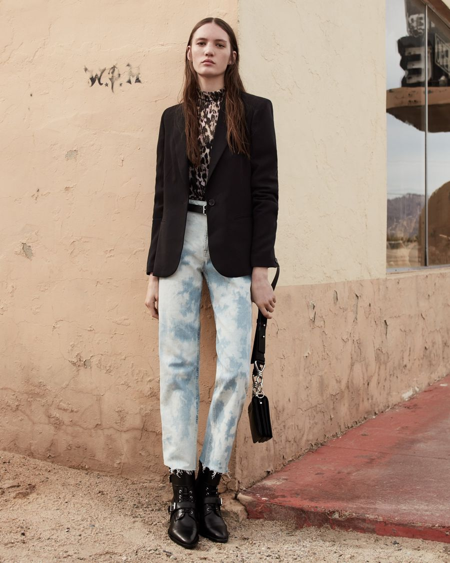 Image of a woman wearing a leopard printed top with a black blazer, acid washed denim jeans and black leather boots.