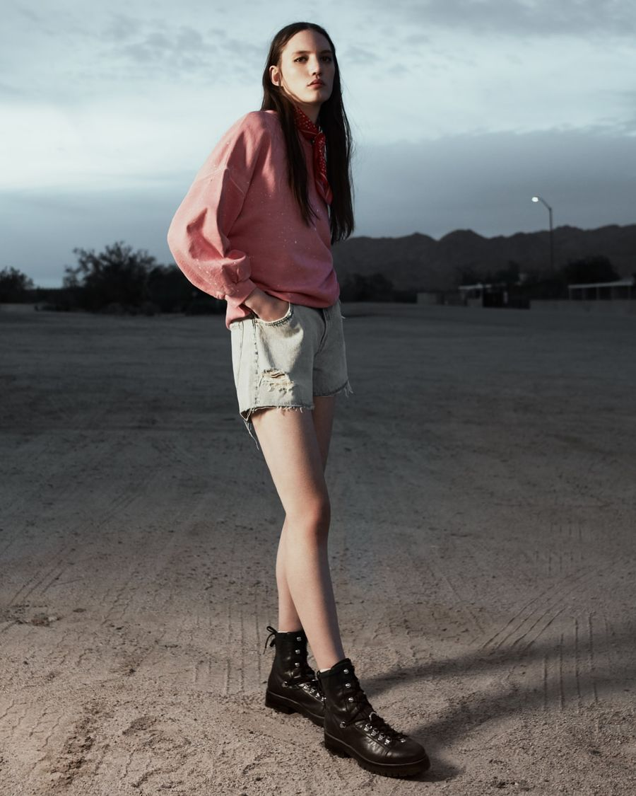 Woman standing in the desert at sunset wearing a light pink sweatshirt with cut off light denim shorts, black leather boots and a red bandana around her neck.