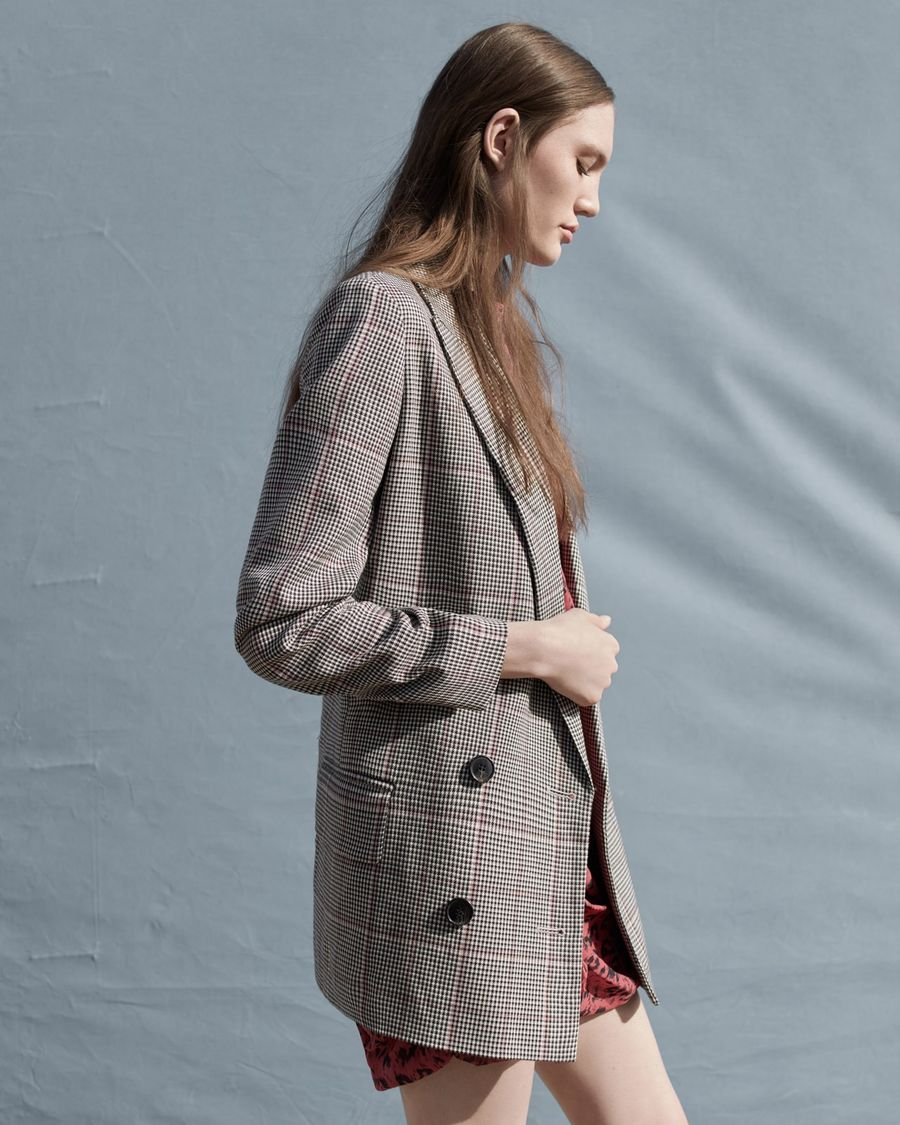 Image of a woman wearing a checked tailored jacket.