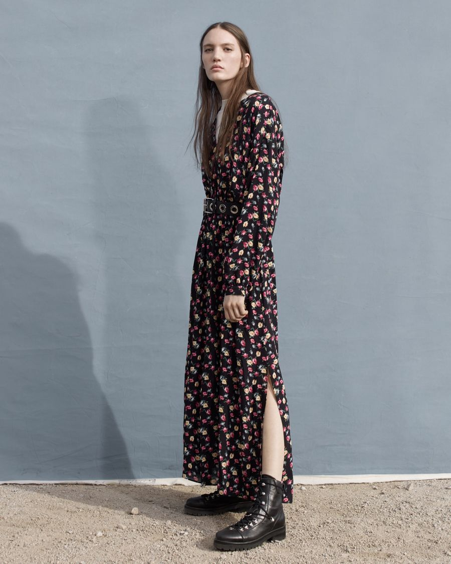 Woman standing in front of a dark grey wall wearing a long flower printed dress with black leather boots.