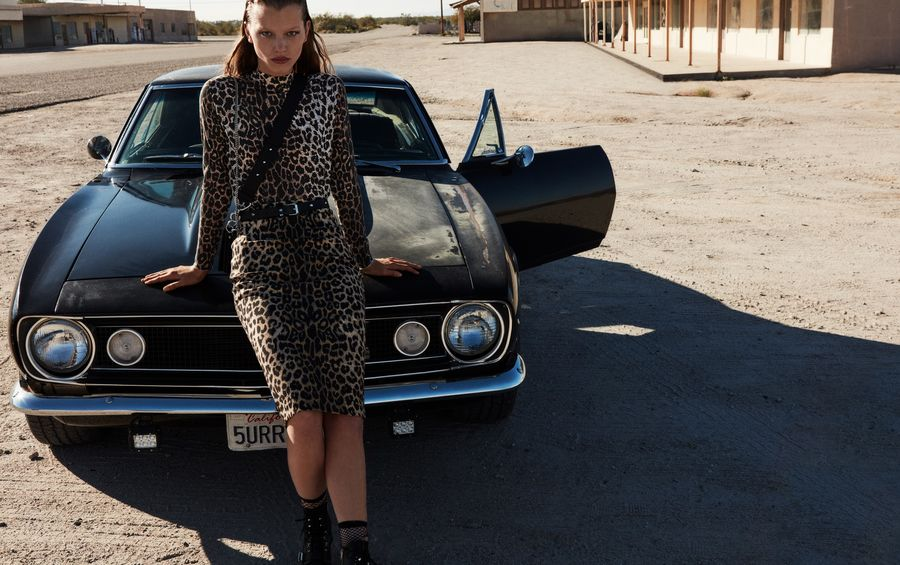 Woman sitting on a black sports car wearing a leopard printed long sleeve top and matching midi skirt with black leather boots, belt and crossbody bag.
