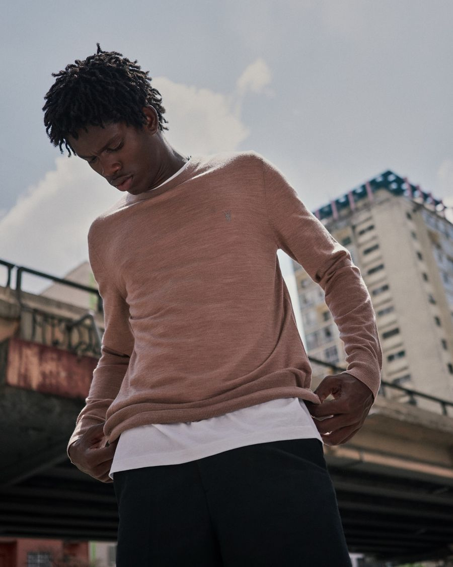 Image of a man standing in front of building wearing a white t-shirt layered with a pink merino jumper worn with dark sweatpants.