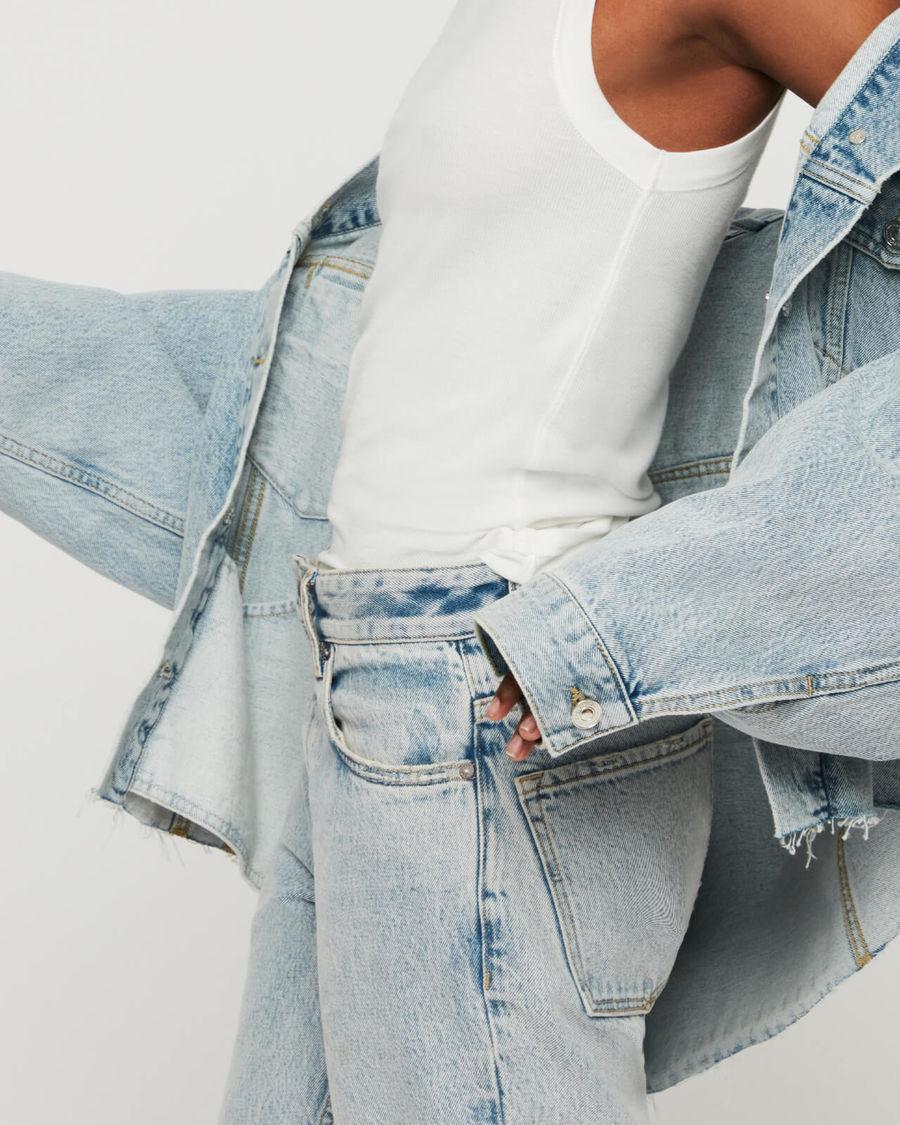 Inquadratura su una donna che indossa un paio di jeans chiari a vita alta con una canotta bianca e una giacca chiara in jeans.