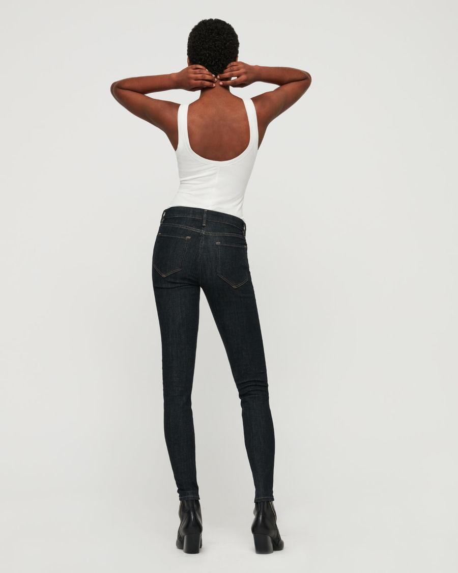 Imagen de una mujer dándole la espalda a la cámara con unos skinny jeans negros, una playera blanca de tirantes y botas negras.