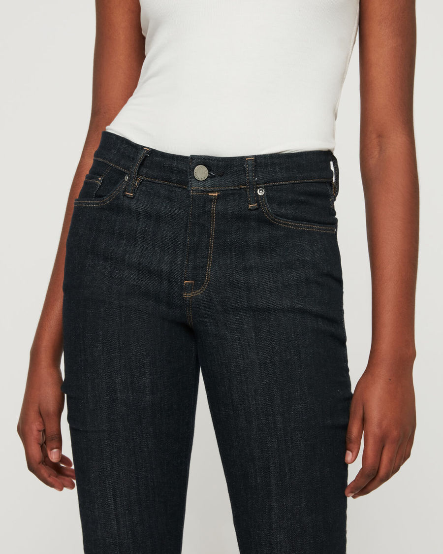 Close-up on a woman's waist wearing a pair of skinny jeans with a white tank.