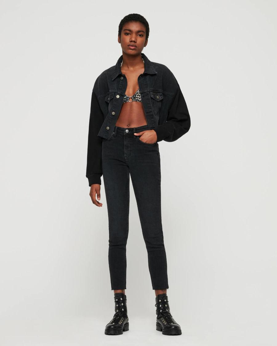 Immagine di una donna ferma in piedi ad un muro bianco. Indossa un paio di jeans scuri a vita alta con un costume leopardato, una giacca corta in jeans e un paio di stivali neri.