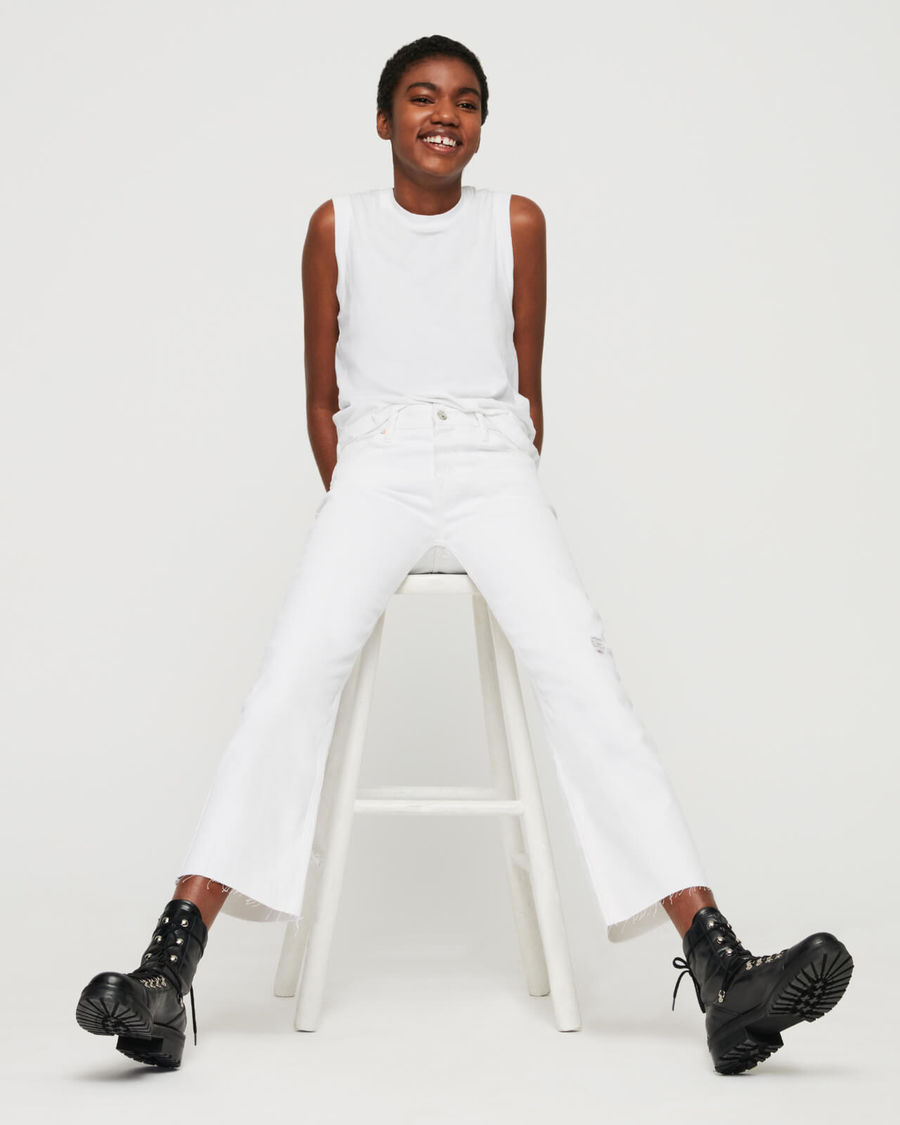 Immagine di una donna che siede su uno sgabello. Indossa un look total-white con un paio di jeans a vita alta, una canotta e un paio di stivali neri.
