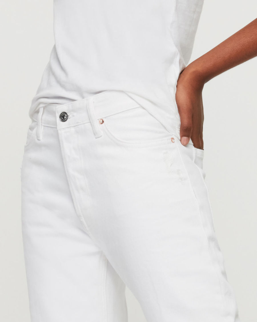 Close-up on a woman's waist wearing a total look white made of a white high waisted pair of jeans and a white tank.