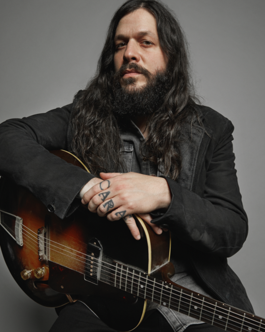 Portrait of Shawn James holding his guitar and wearing a grey denim shirt with a black leather blazer.