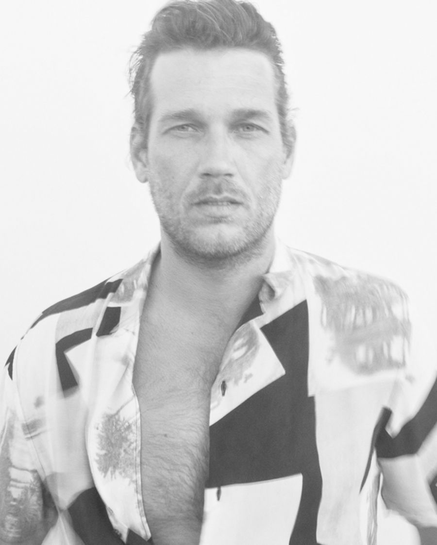 Black and white portrait of a man wearing a printed Hawaiian shirt.