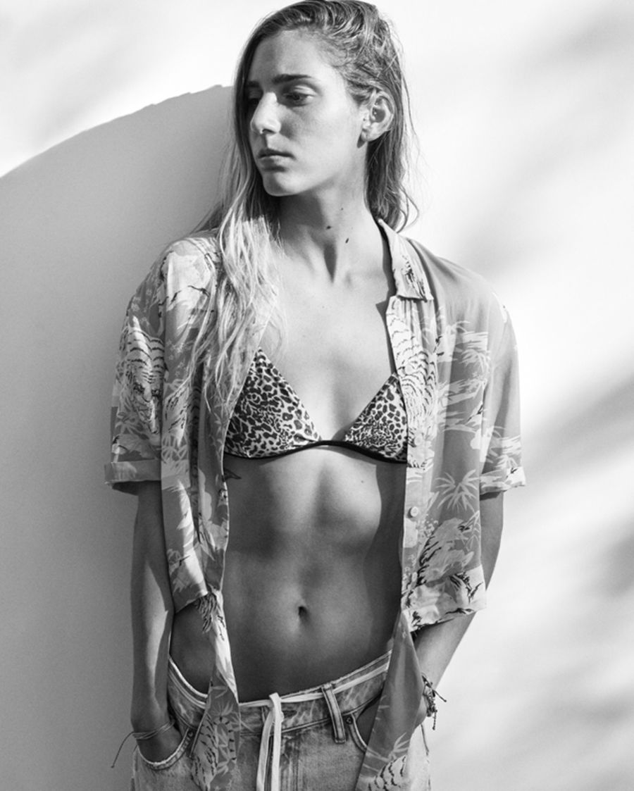 Black and white image of a woman wearing a leopard bikini top, printed Hawaiian shirt and light denim jeans.