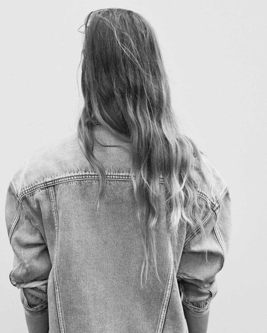 Black and white back shot of a woman wearing an oversized denim jacket.
