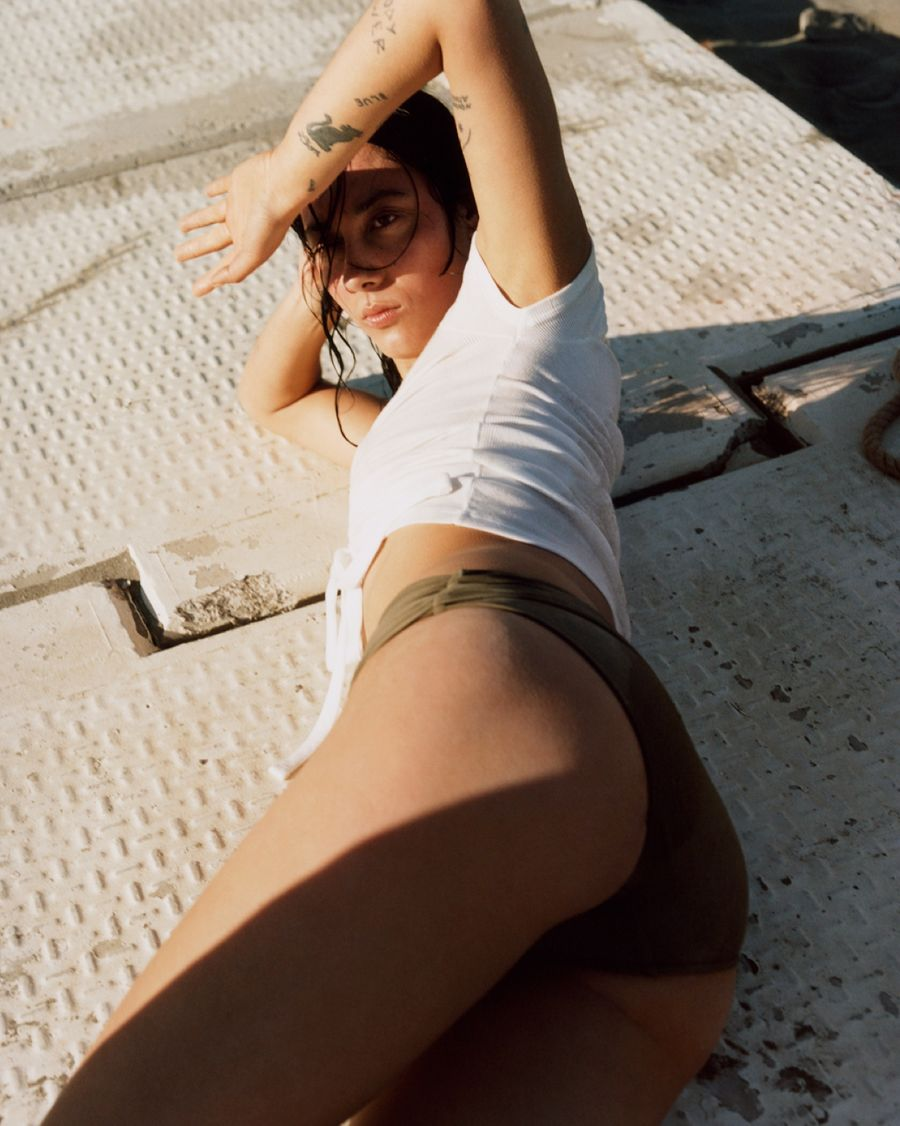 Image of a girl lying on the floor wearing a white crop top with a khaki bikini bottom.
