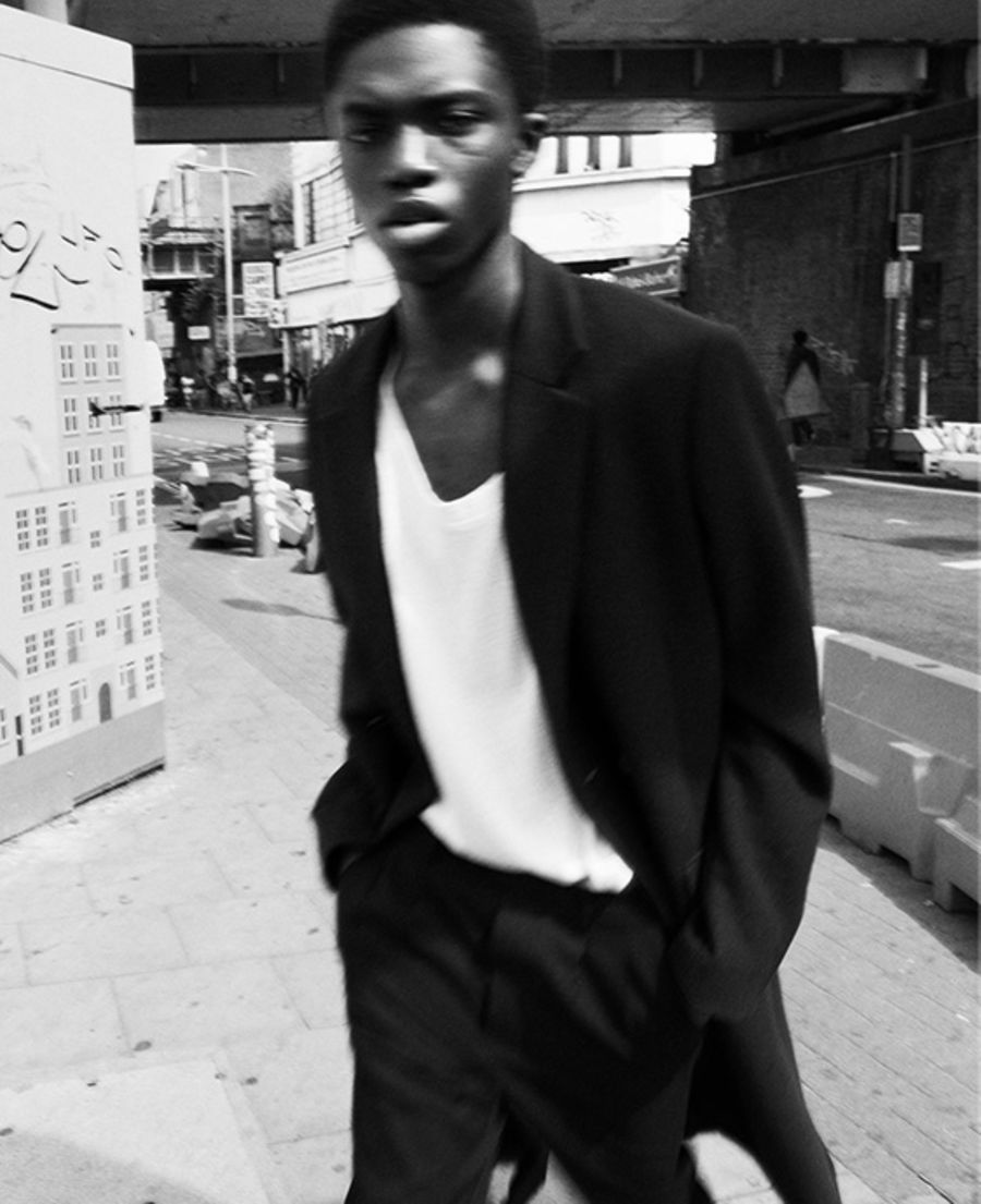 Series of four black and white images of a man walking in the street, wearing dark trousers with a dark coat and a white t-shirt.