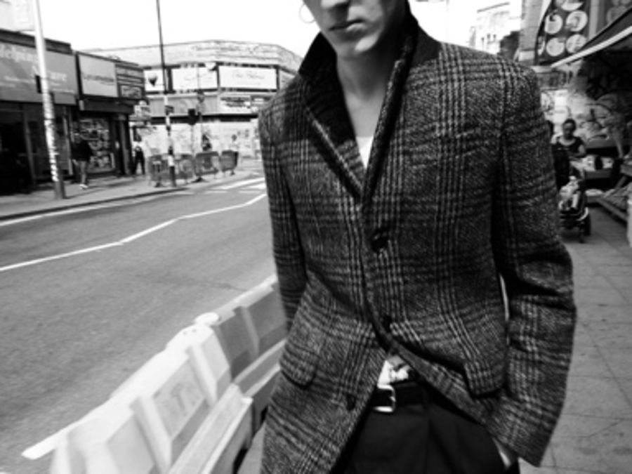 Black and white image of a man walking in the street wearing a long checked coat.