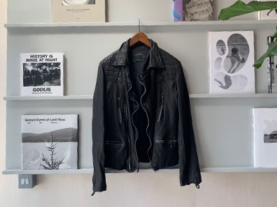 Image of a black leather jacket hanging from a shelf with books and magazines on.