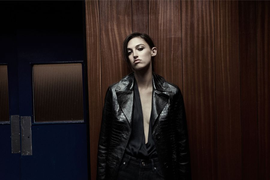 Image of a woman in front of a wooden wall wearing a croco patterned black leather jacket with a black silky top and black jeans.