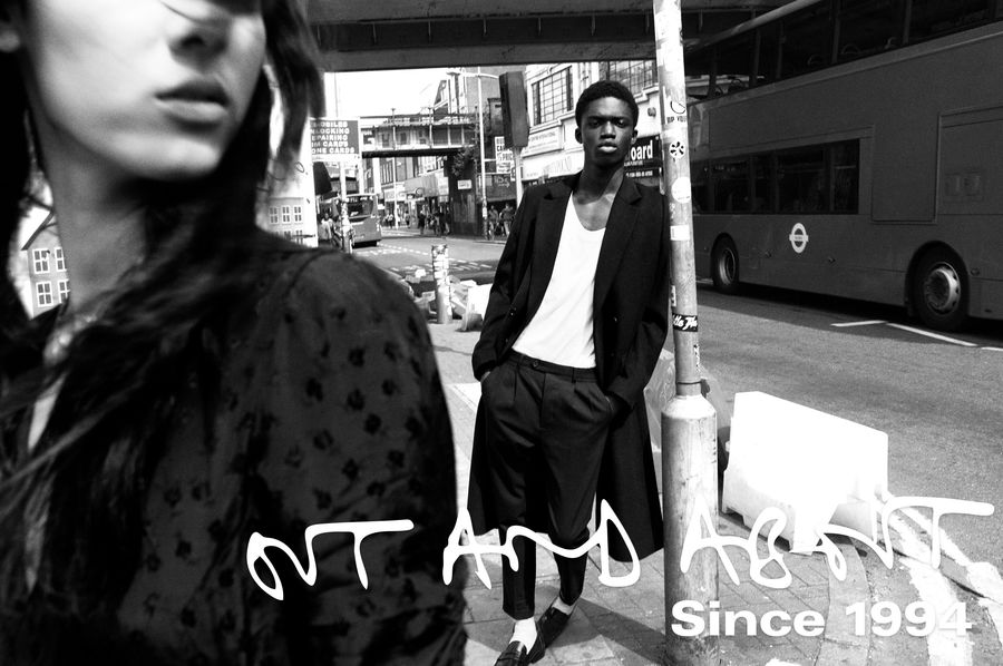 Black and white image of a woman and a man in the street wearing items from our latest collection.