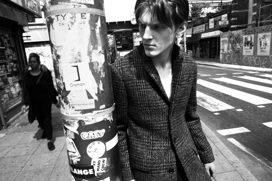 Black and white image of a man standing in a street, wearing a closed checked coat.