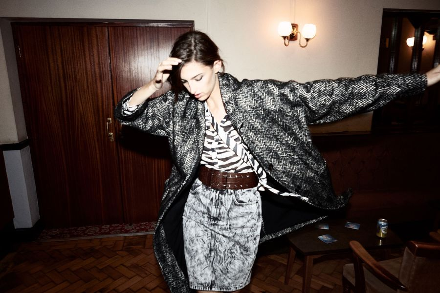 Image of a woman in a corridor wearing a grey textured pencil skirt with a brown leather belt, a zebra printed shirt and a black and white coat.