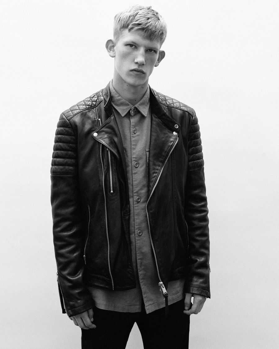 Black and white campaign image of a man wearing a black leather biker jacket over a buttonned up shirt.