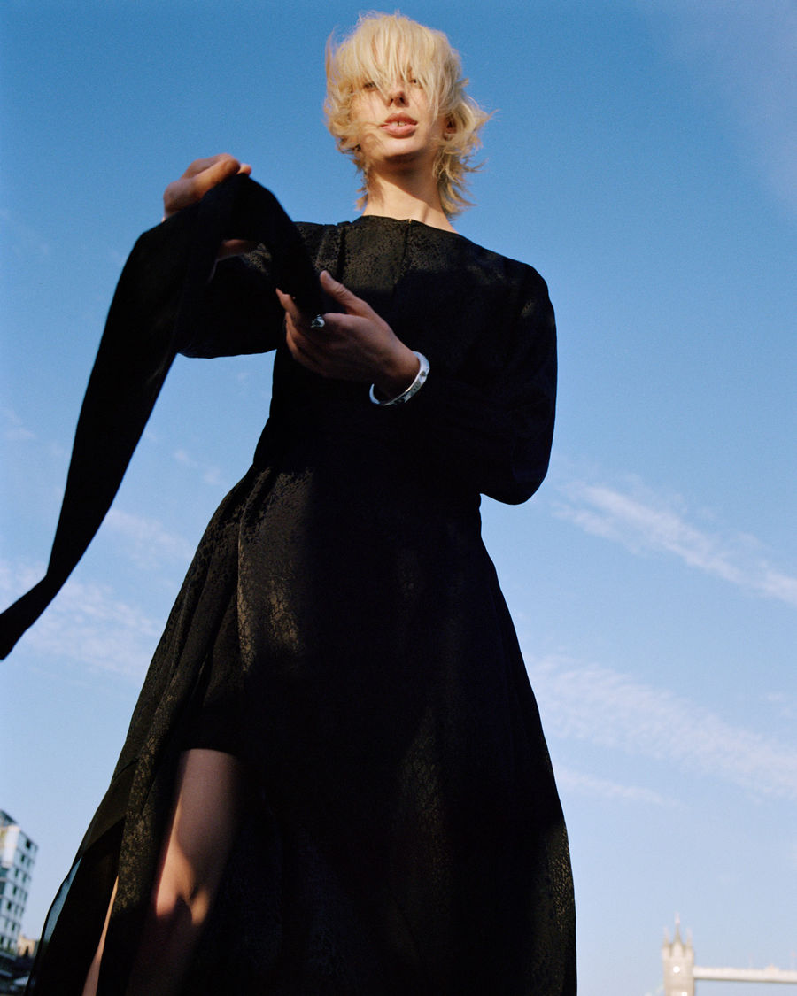 Campaign image of a woman standing outside in London wearing a long sleeve black dress.