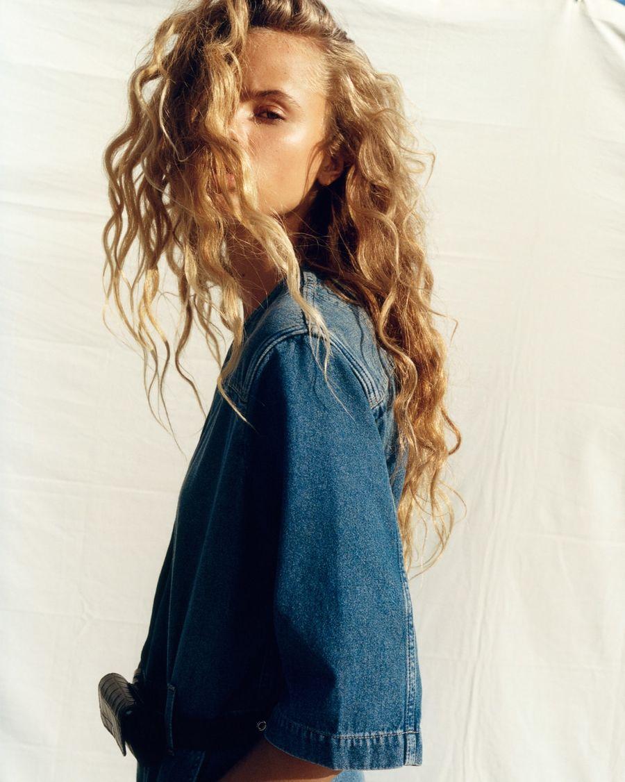 Portrait of a woman wearing a denim jumpsuit.