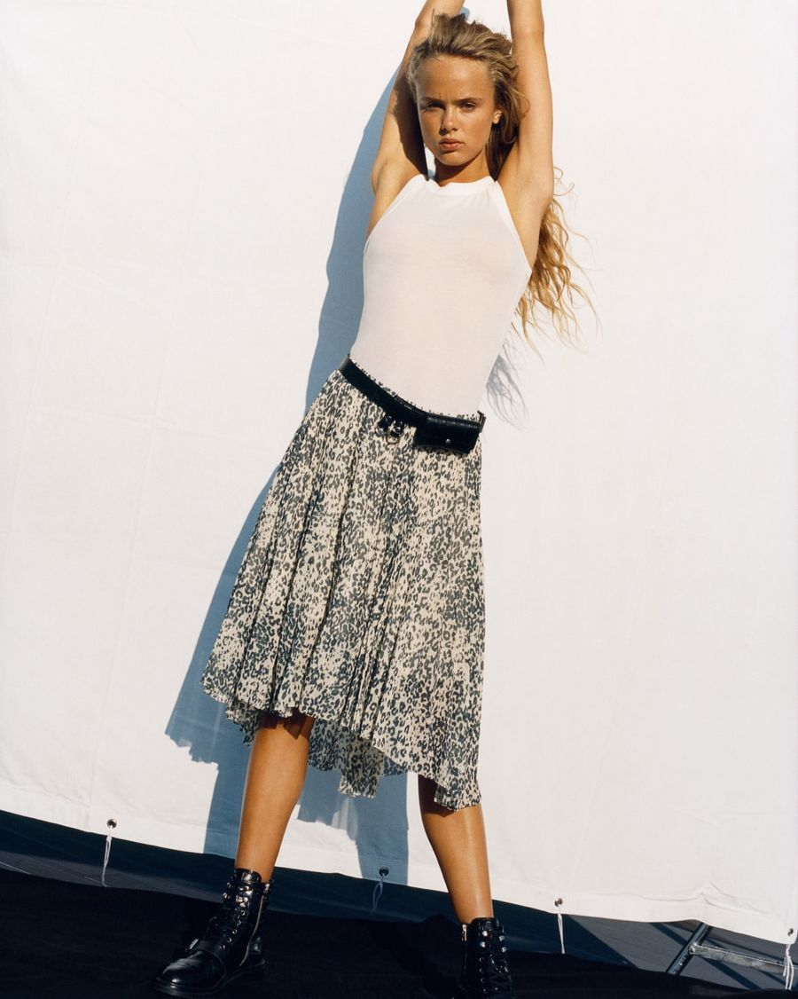 Image of a girl wearing a white vest with a leopard skirt, a mini black bumbag and black leather boots.