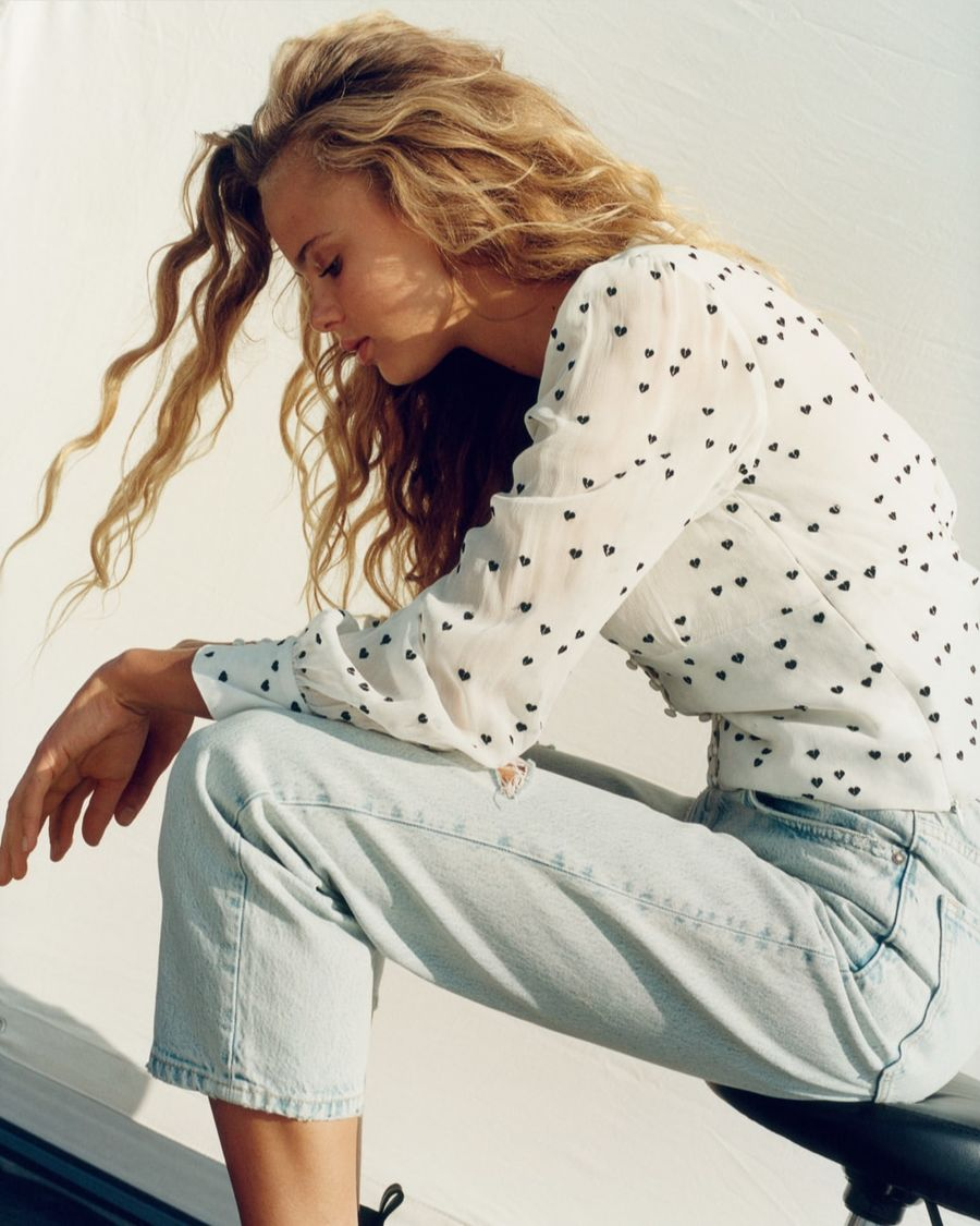 Image of a woman sitting on a chair wearing a black and white heart printed shirt with light denim jeans.
