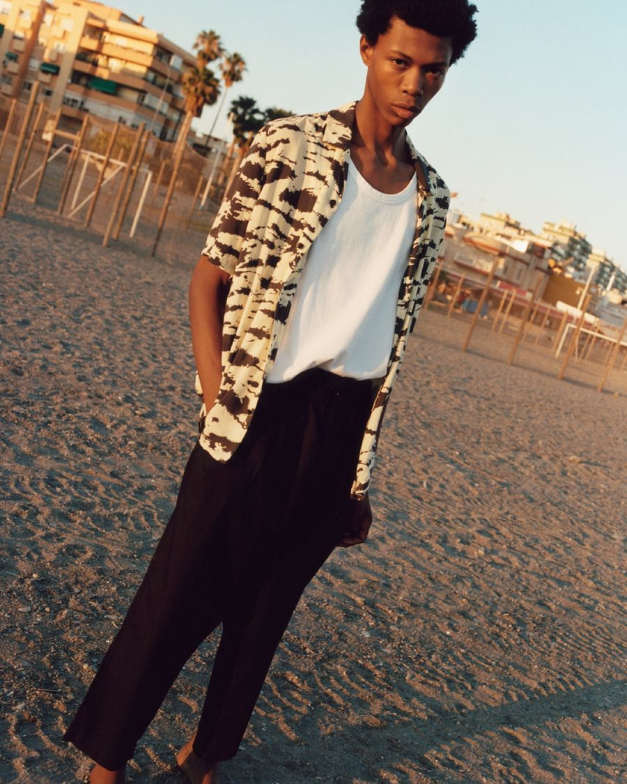 Portrait of a man standing on the beach at sunset wearing a white vest with a black and white tiger printed shirt and black trousers.