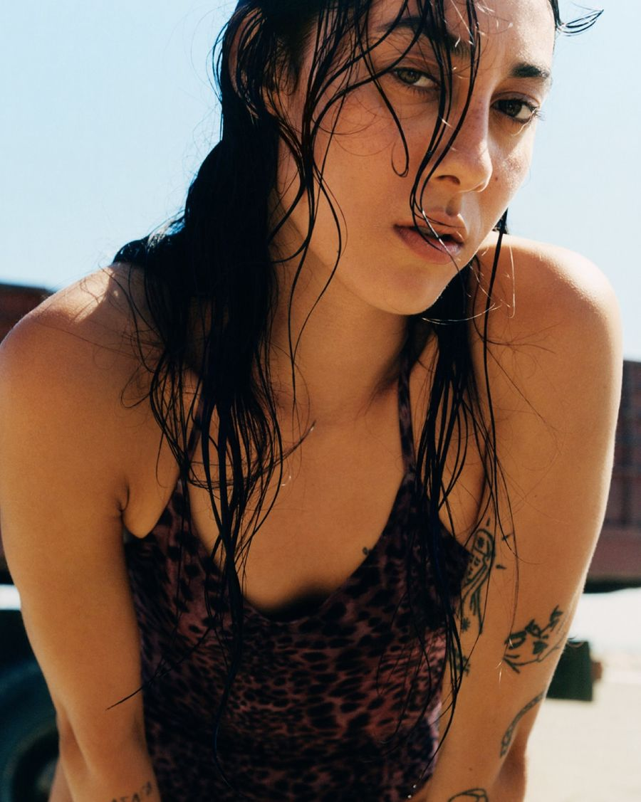 Portrait of a woman staring at the camera and wearing a purple leopard printed swimsuit.