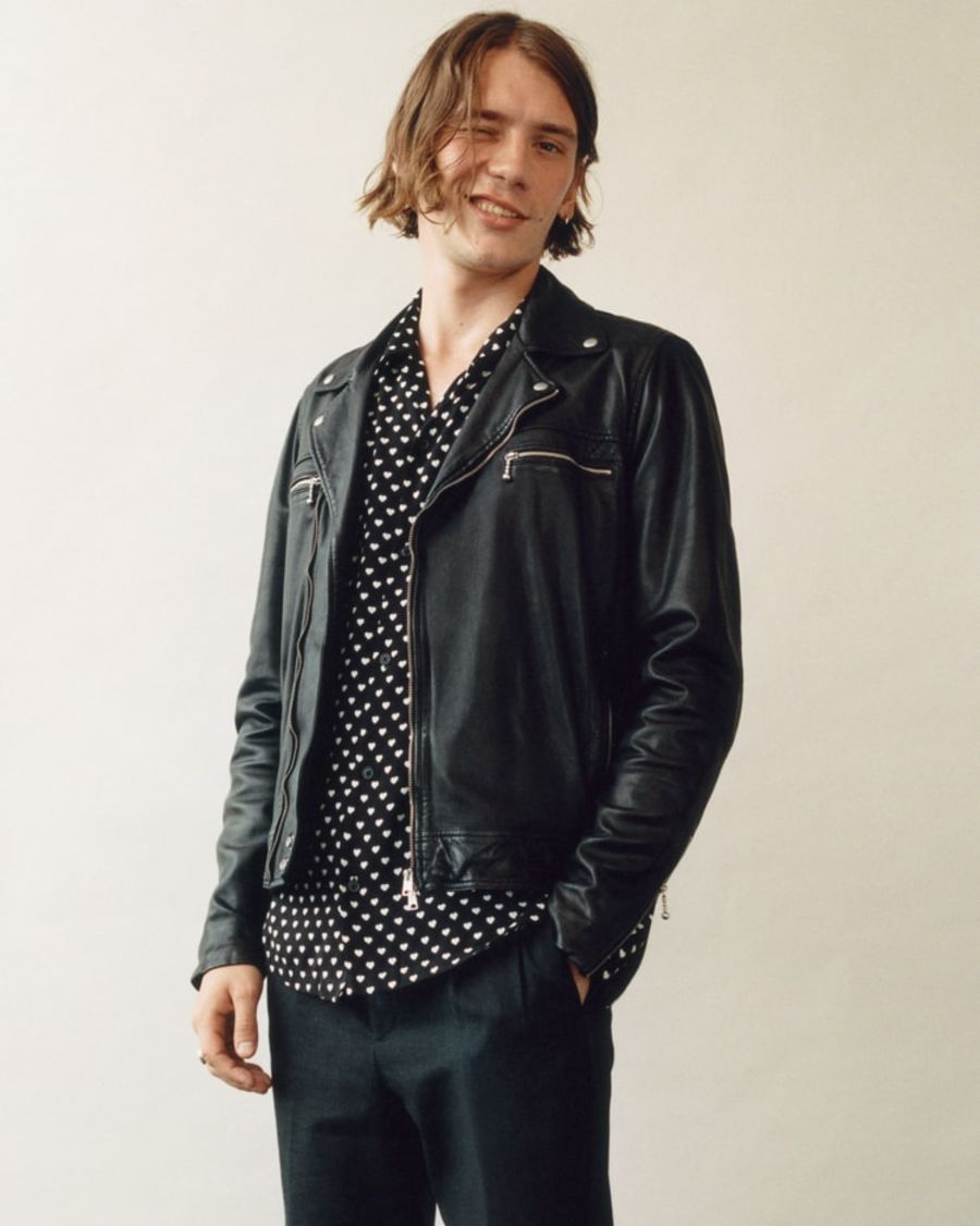 Image of a man wearing a black leather jacket with a black and white heart printed shirt and black tailored trousers.