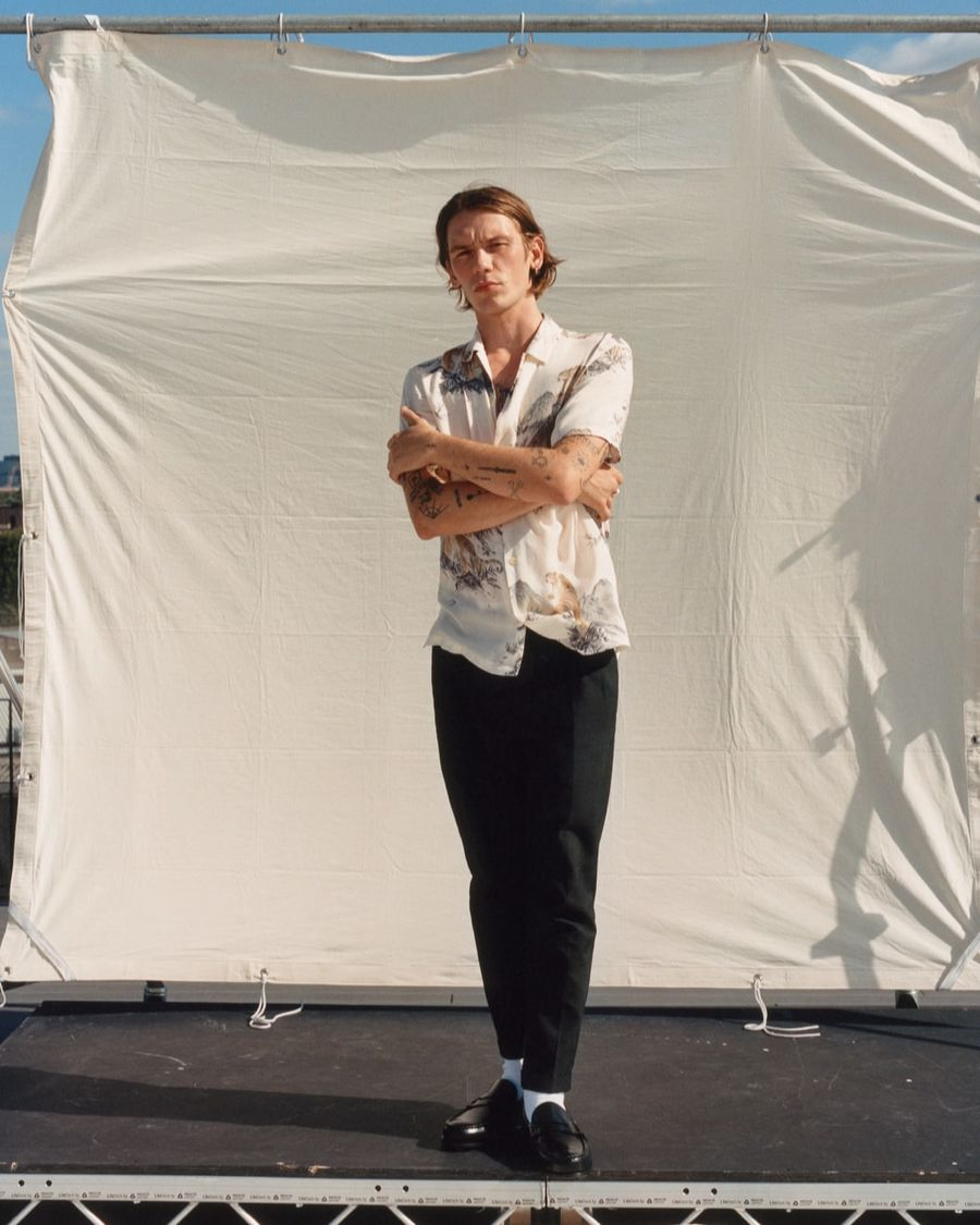 Image of a man folding his arms wearing a light hawaiian shirt with black trousers, white socks and black loafers.