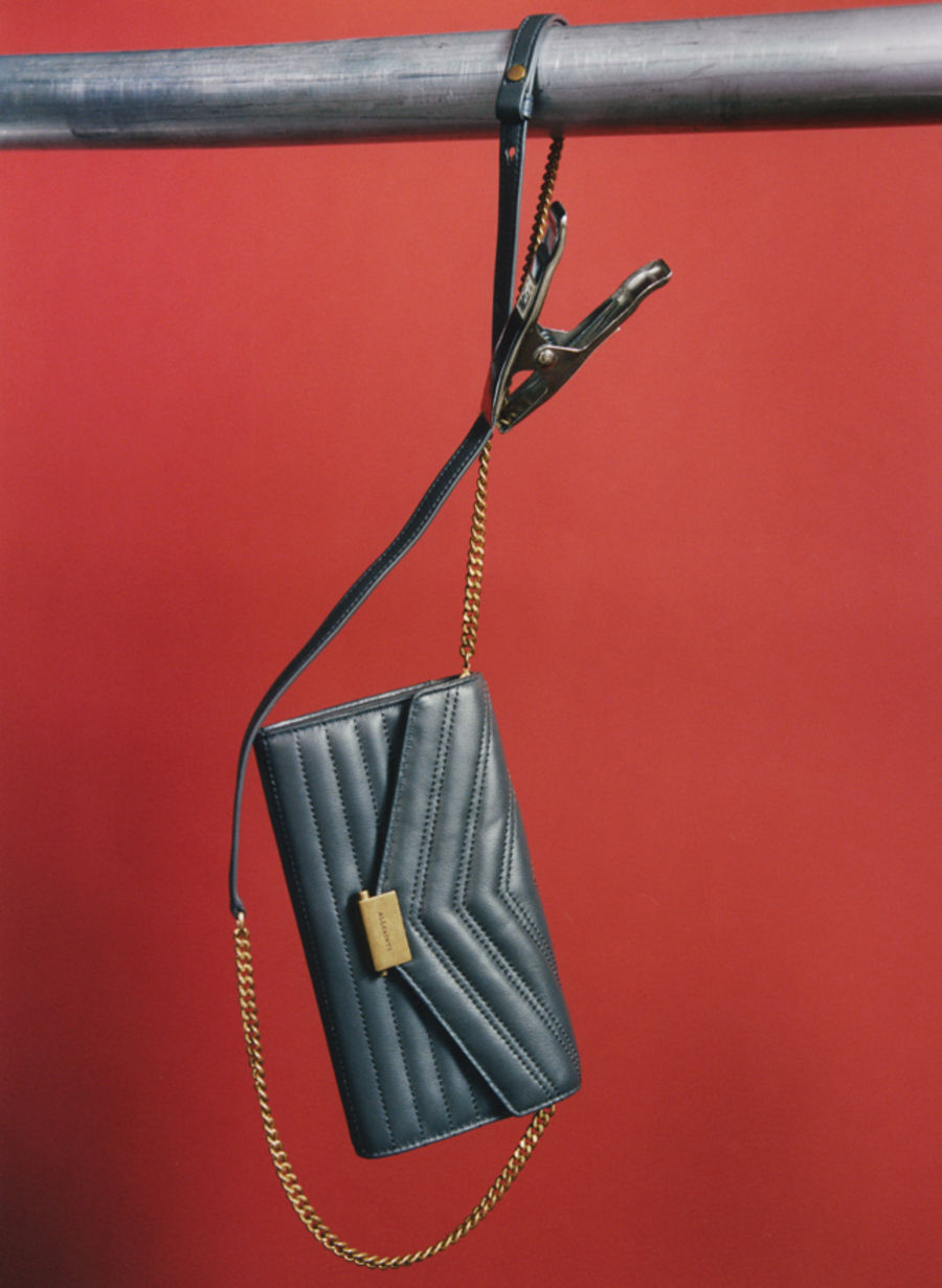 Image of a grey leather bag suspended in front of a red wall.