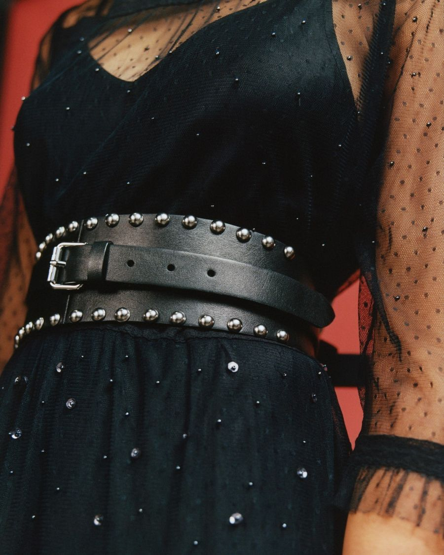Close-up on a woman's waist. She wears a black mesh dress with a black studded leather belt.