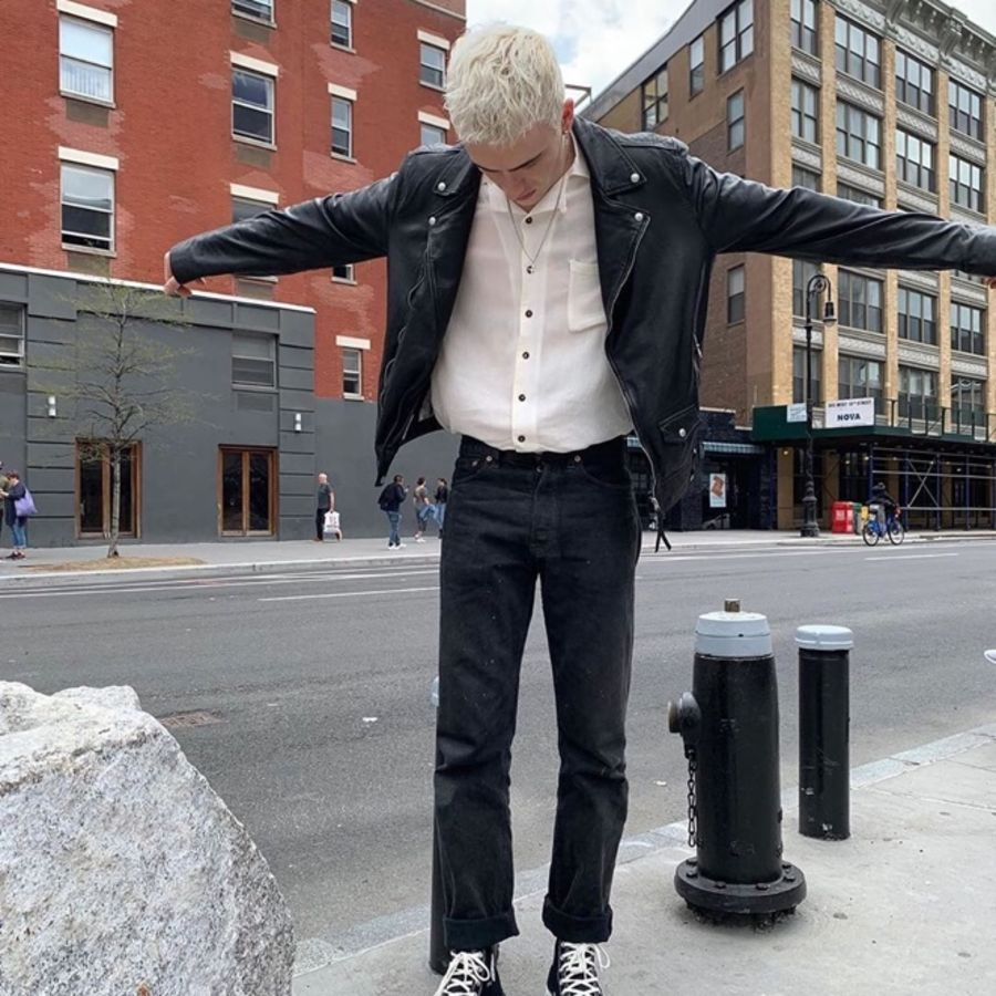 Image of a man wearing a leather jacket in the street.