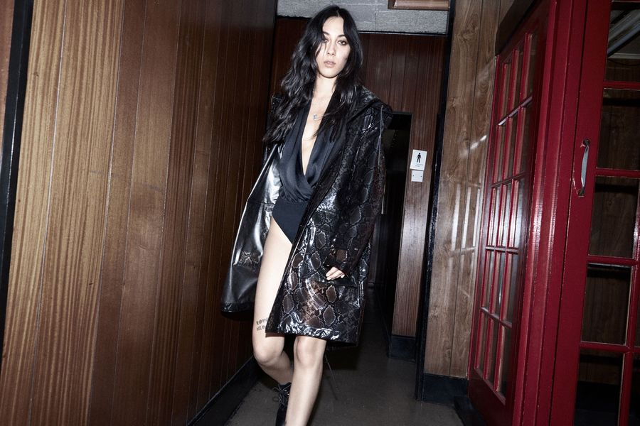 Imagen de una mujer caminando por un corredor vistiendo un body negro sedoso y un abrigo largo de cuero con estampado de piel de serpiente.
