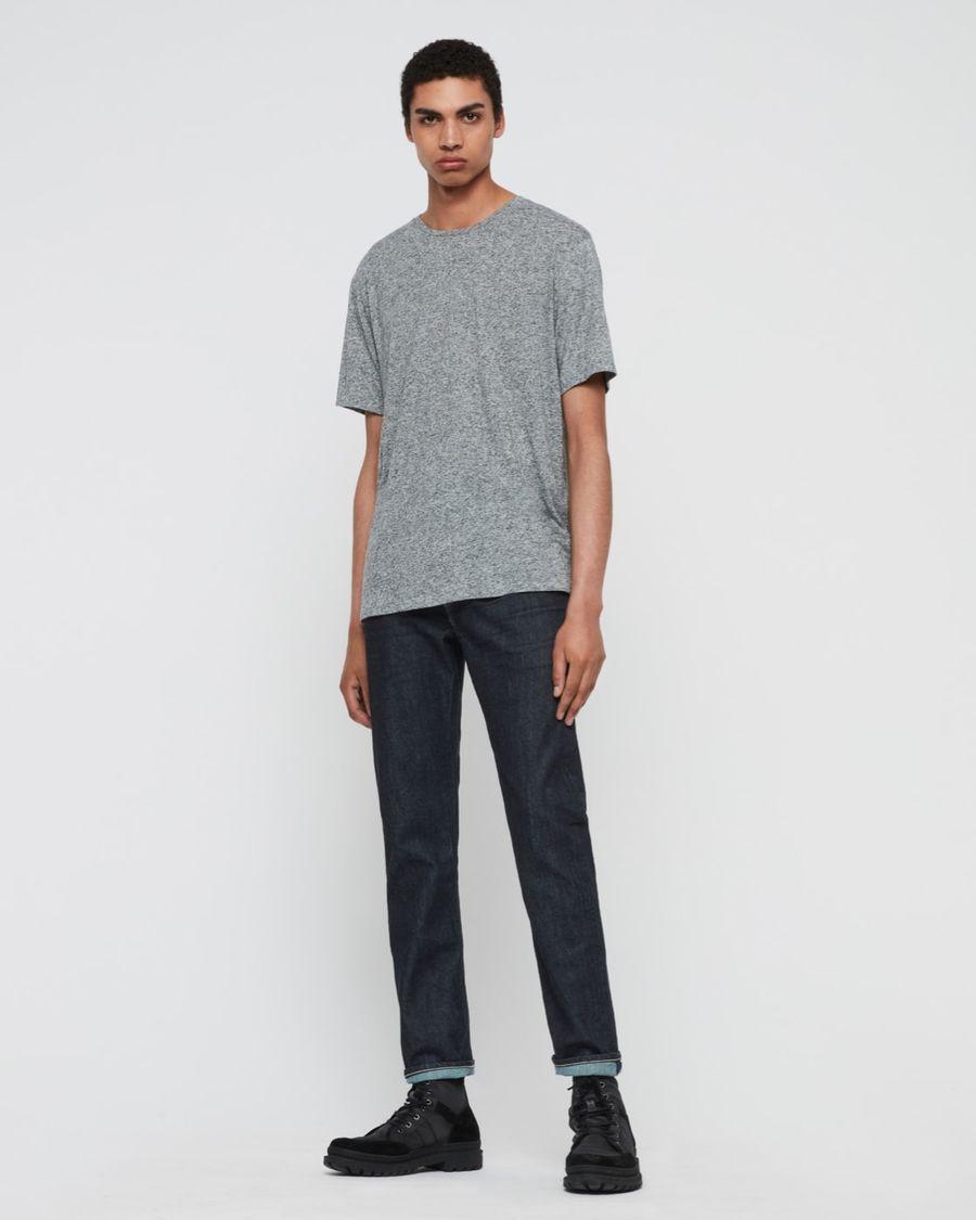 Foto von einem Mann, der dunkelblaue gerade Jeans, ein hellgraues T-Shirt und schwarze Stiefel trägt.