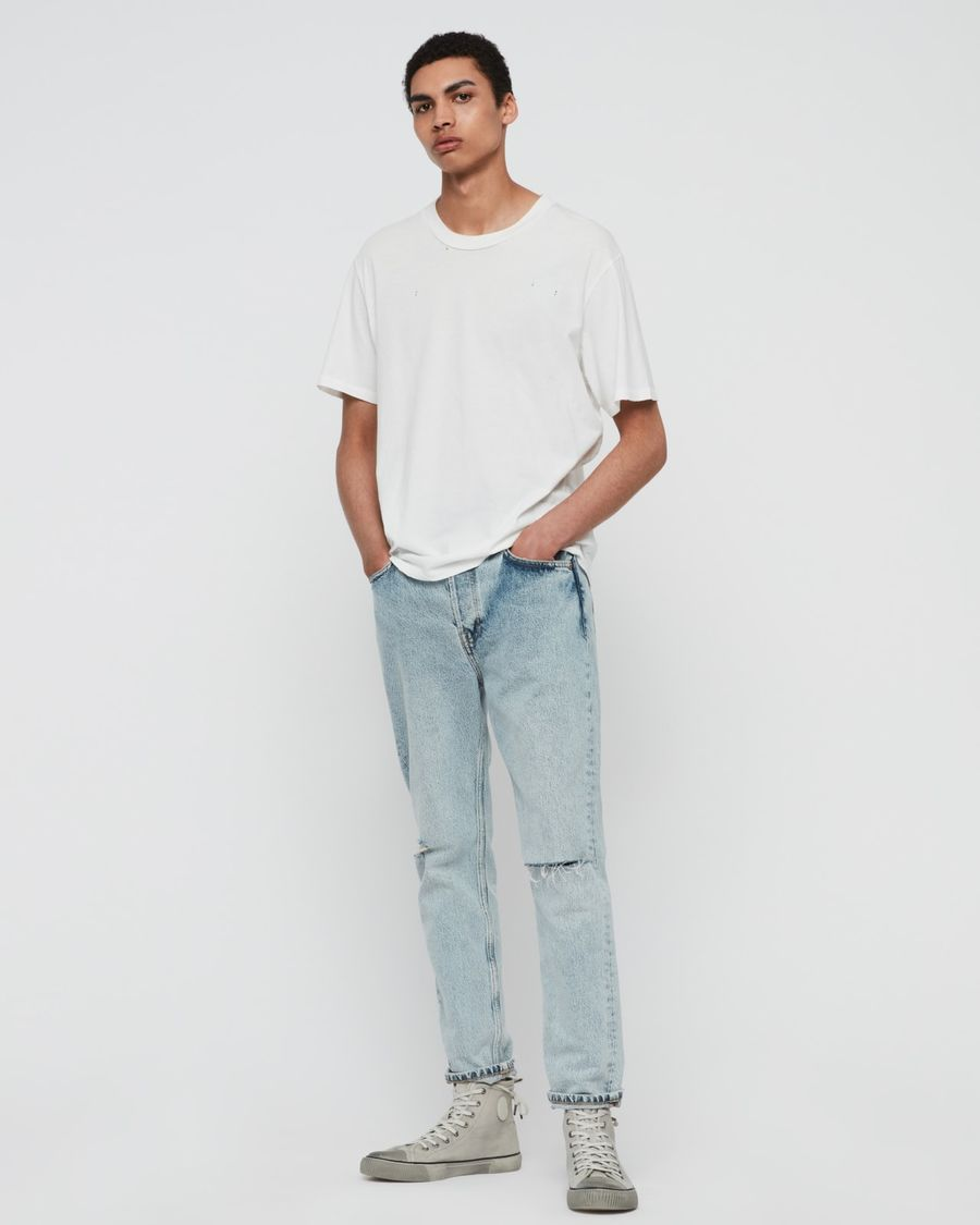 Image of man standing in front of a white wall wearing a pair of light denim jeans with a white t-shirts and trainers.
