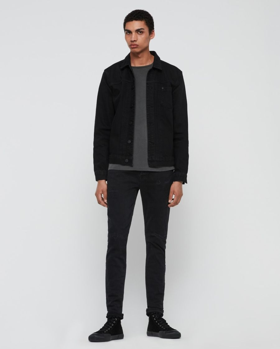 Foto von einem Mann, der schwarze Skinny Jeans, eine schwarze Jeansjacke, ein dunkelgraues T-Shirt und schwarze Turnschuhe trägt.