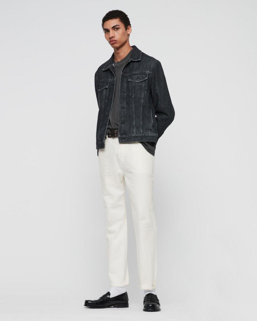 Foto von einem Mann, der weiße Jeans mit einem dunkelgrauen T-Shirt, einer dunkelblauen Jeansjacke und schwarzen Loafern trägt.