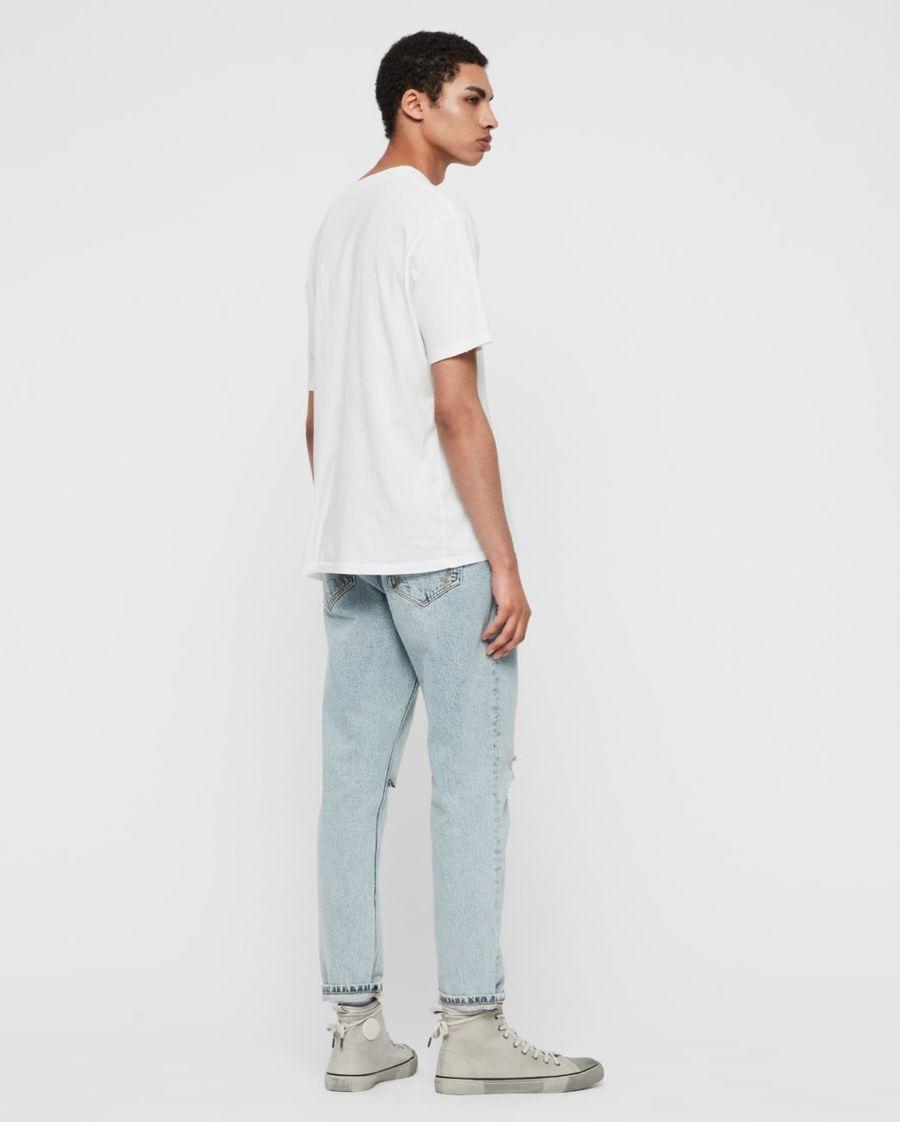 Foto von einem Mann, der ein Paar helle Jeans, ein weißes T-Shirt und Turnschuhe trägt.