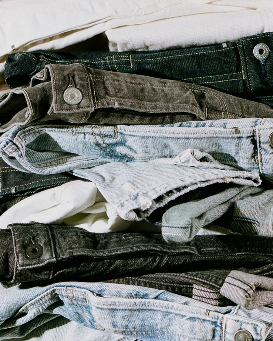 Close up of a pile of our folded jeans in different styles and colours.