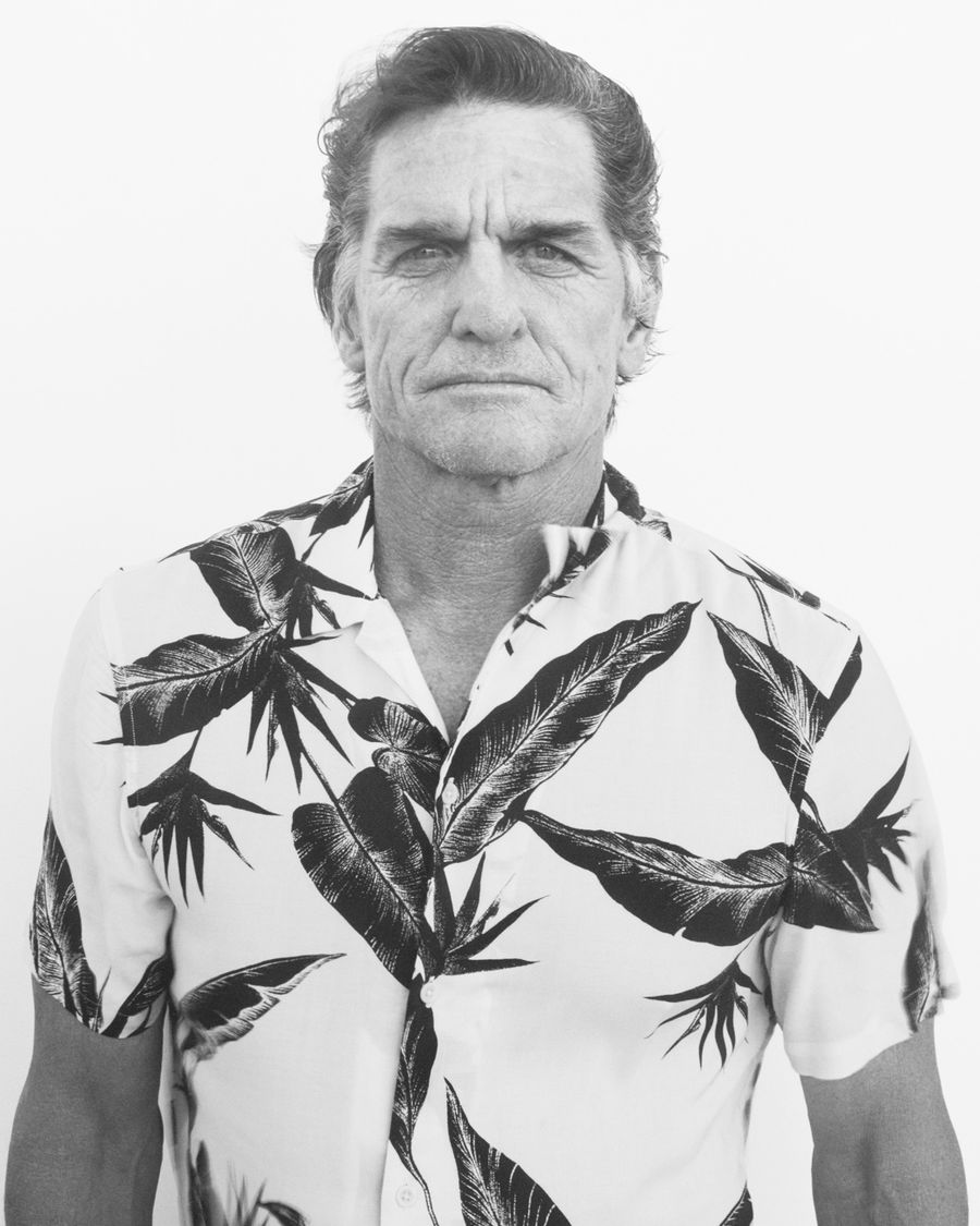 Black and white portrait of an older man wearing a printed Hawaiian shirt.