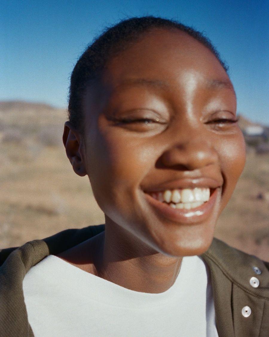 Gros plan sur une femme souriant à la caméra portant un t-shirt blanc avec une veste kaki.