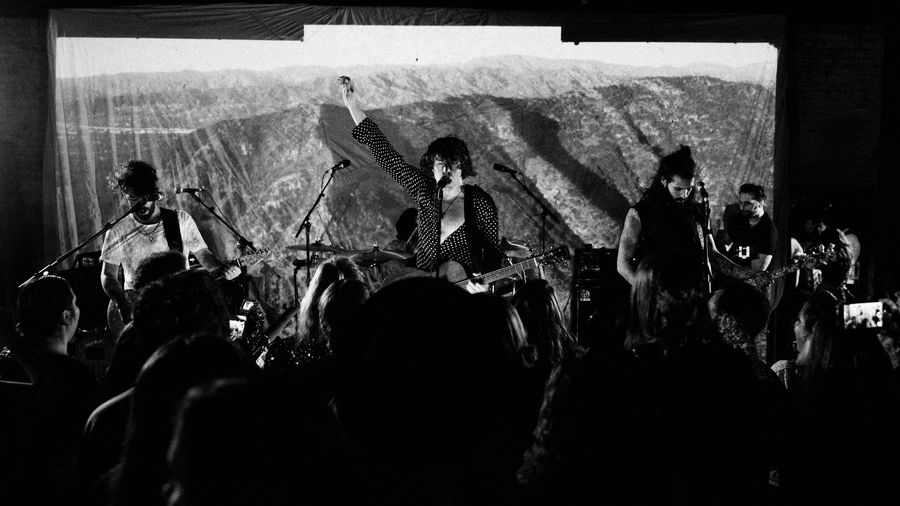 Black and white images of Barns Courtney singing on stage with his band.