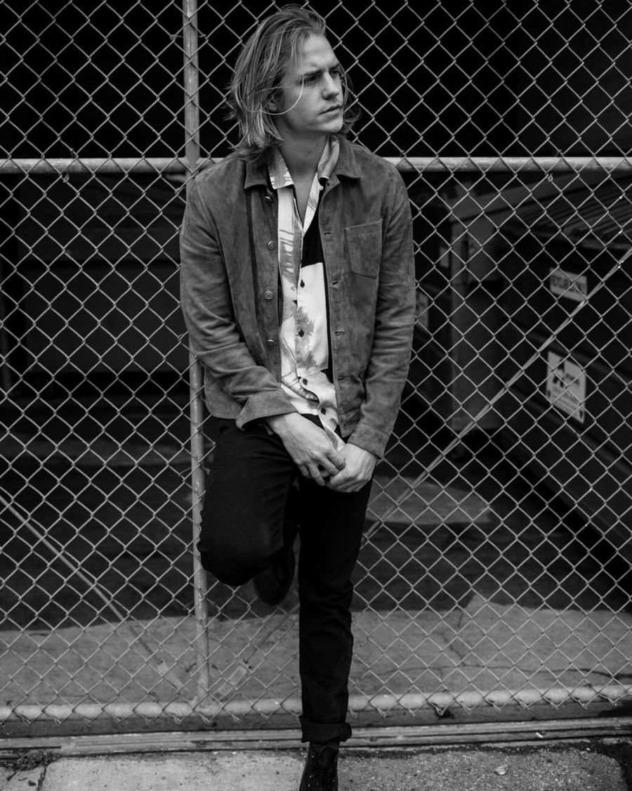 Black and white picture of Corey Harper leaning on a wire fence and wearing pieces from our last collection.