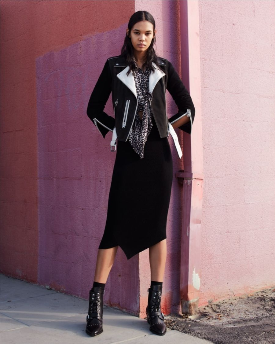 Image of a woman posing in front of a pink wall in the street and wearing a black cotton skirt with a leopard tied up shirt, dark leather jacket and black leather studded shoes.
